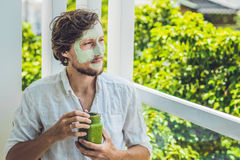 Spa man applying Facial green clay Mask. Beauty Treatments. Fresh green smoothie with banana and spinach with heart of sesame seed Stock Image