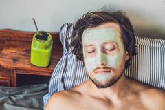 Spa man applying Facial green clay Mask. Beauty Treatments. Fresh green smoothie with banana and spinach with heart of sesame seed Stock Photos
