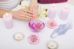 Spa Manicure. Woman Hands With Perfect Natural Healthy Nails Soaking In Aroma Hand Bath. Closeup Of Glass Bowl With Water And Blu Stock Images