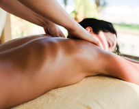 Spa Massage. Young woman getting massage at the resort's spa center Royalty Free Stock Image