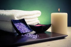 Spa massage border background with towel stacked, candle and sea salt Royalty Free Stock Photo
