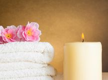 Spa massage border background with towel stacked and candle Royalty Free Stock Images