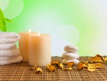Spa massage border background with towel stacked, candles and perfumed leaves Royalty Free Stock Photo