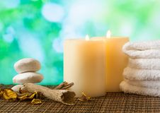 Spa massage border background with towel stacked, candles and perfumed leaves Stock Image