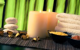 Spa massage border background with towel stacked, candles and sea salt Stock Photos