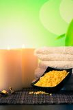 Spa massage border background with towel stacked, candles and sea salt Royalty Free Stock Photo