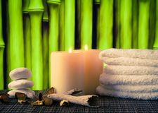 Spa massage border background with towel stacked, candles and stone Stock Photos