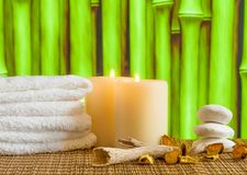 Spa massage border background with towel stacked, candles and stone Royalty Free Stock Images