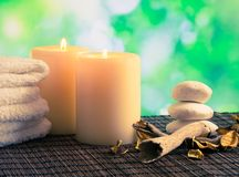 Spa massage border background with towel stacked, candles and stone Stock Photo