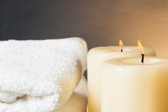 Spa massage border background with towel stacked and candles Royalty Free Stock Images
