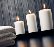 Spa massage border background with towel stacked and candles Royalty Free Stock Photography