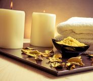 Spa massage border background with towel stacked, perfumed leaves, candle and sea salt Royalty Free Stock Photography
