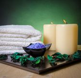 Spa massage border background with towel stacked, perfumed leaves, candle and sea salt Stock Images