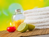 Spa massage border background with towel stacked,red candle and lime Stock Photos