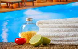 Spa massage border background with towel stacked,red candle and lime near swimming pool Royalty Free Stock Photography