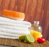 Spa massage border background with towel stacked red candle and lime Royalty Free Stock Image