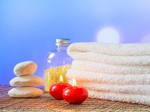 Spa massage border background with towel stacked,red candles and stone Stock Photography