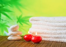 Spa massage border background with towel stacked,red candles and stone Royalty Free Stock Image