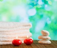 Spa massage border background with towel stacked,red candles and stone Royalty Free Stock Photo