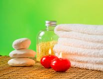 Spa massage border background with towel stacked,red candles and stone Royalty Free Stock Images