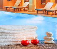 Spa massage border background with towel stacked,red candles and stone near swimming pool Stock Image