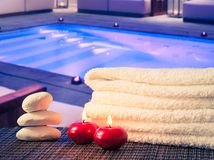 Spa massage border background with towel stacked,red candles and stone near swimming pool Stock Photography