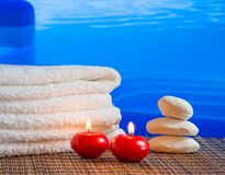 Spa massage border background with towel stacked,red candles and stone near swimming pool border Stock Photos