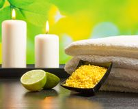 Spa massage border background with towel stacked sea salt candles and lime Royalty Free Stock Photos