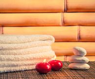 Spa massage border background with towel stacked stone and red candles Stock Image