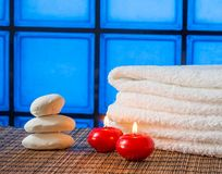Spa massage border background with towel stacked stone and red candles warm atmosphere Royalty Free Stock Images