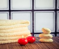 Spa massage border background with towel stacked stone and red candles warm atmosphere Royalty Free Stock Photos