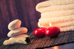 Spa massage border background with towel stacked stone and red candles warm atmosphere Stock Image