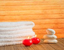 Spa massage border background with towel stacked stone and red candles warm atmosphere Royalty Free Stock Photography