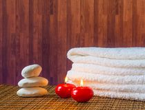 Spa massage border background with towel stacked stone and red candles warm atmosphere Stock Photo