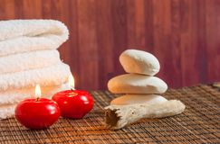 Spa massage border background with towel stacked stone and red candles warm atmosphere Stock Images