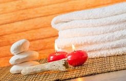 Spa massage border background with towel stacked stone and red candles Royalty Free Stock Photo
