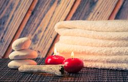 Spa massage border background with towel stacked stone and red candles Royalty Free Stock Photography