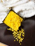 Spa massage border background with towel stacked and yellow sea salt Royalty Free Stock Image