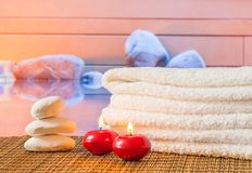 Spa massage border with towel stacked,red candles near stone Royalty Free Stock Photo