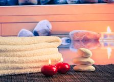Spa massage border with towel stacked,red candles near stone Stock Photos