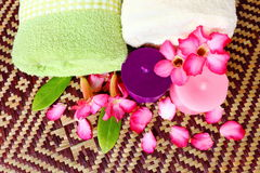 Spa massage healthy setting. With rolled towel,candlelight and beautiful flower on mat Stock Photo