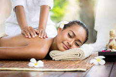 Spa massage outdoor. Balinese woman receiving back massage royalty free stock photography