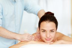 Spa massage. Serene girl enjoying massage in beauty spa salon and looking at camera royalty free stock photography