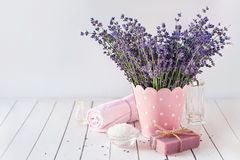 Spa massage setting, lavender product, oil on wooden background. Spa resort and wellness composition - lavender flowers, coloured bathing soap and salt Stock Photo
