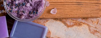 Spa massage setting, lavender product, oil on wooden background. Soap lavender flavored salt violet color, Copy space, top view. Long wide banner royalty free stock photos