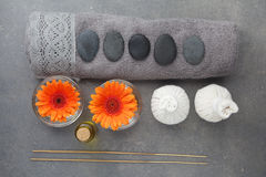 Spa massage setting with rolled towel, thai herbal compress balls and flowers. Flat lay. Top view Stock Images
