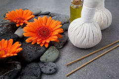 Spa massage setting with rolled towel, thai herbal compress balls and flowers Royalty Free Stock Photography