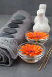Spa massage setting with rolled towel, thai herbal compress balls and flowers Royalty Free Stock Images