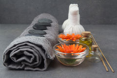 Spa massage setting with rolled towel, thai herbal compress balls and flowers Royalty Free Stock Photos