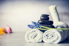 Spa massage setting with towels, hot stones and blue flowers, close up, wellness concept. Front view stock images